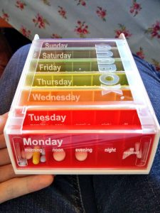 Rainbow-coloured medication weekly box