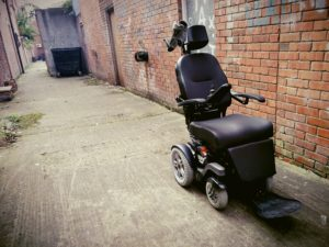 Ellen's electric wheelchair parked in a back alleyway off a street in Belfast