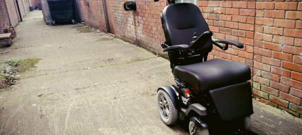 An electric wheelchair parked in a back alleyway in Belfast