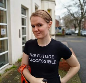 Ellen standing outside the Belfast Trans Resource Centre wearing a black THE FUTURE IS ACCESSIBLE tshirt and holding an orange crutch